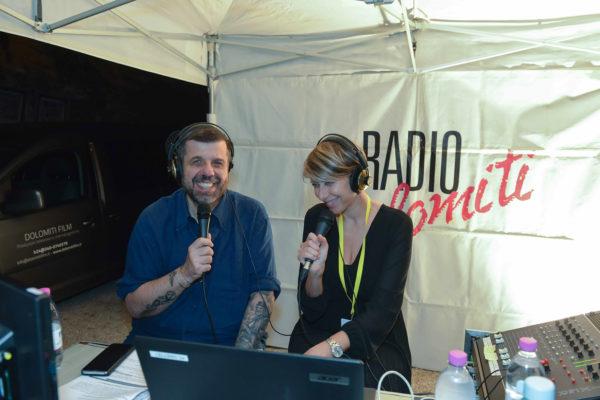 Due presentatori radiofonici con microfono in mano