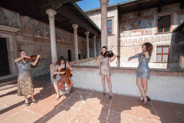 4 ragazze suonano in un loggiato