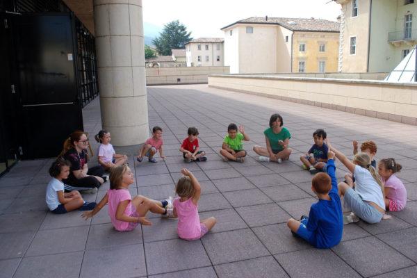 Bambini seduti in cerchio sul terrazzo del Mart di Rovereto